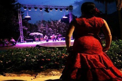 Flamenco Dancer in red dress in front of stage